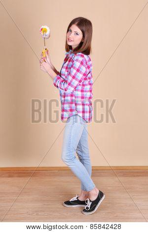 Beautiful girl with roller near wall