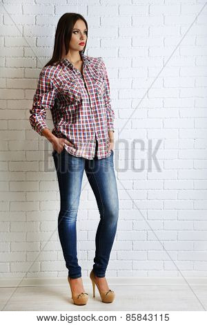 Pretty girl dressed in casual style posing on white brick wall background