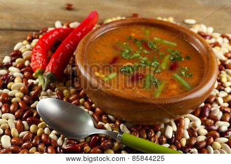 Bean soup in bowl and raw beans on wooden table background