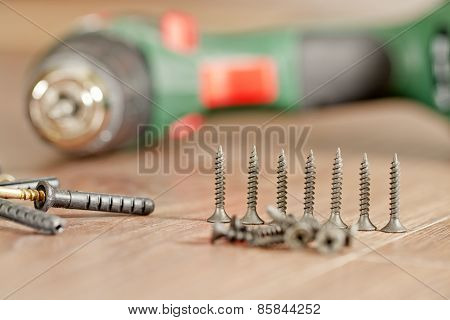 screws and fasteners lie on the background of the screwdriver