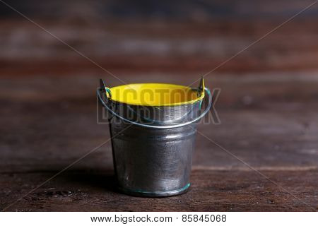 Metal bucket with colorful paint on wooden background