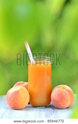 glass of delicious peach juice and peaches on table in garden