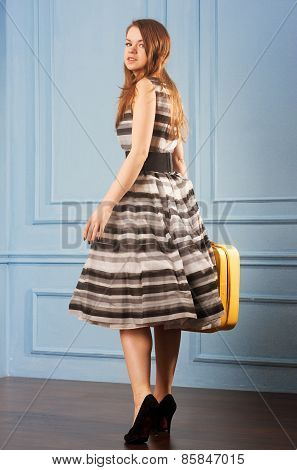 Girl In Magnificent Dress With A Yellow Suitcase Near Blue Wall