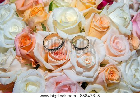 Wedding rings in a bouquet of roses.