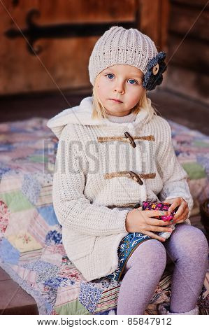 vertical portrait of adorable blonde child girl in beige knitted hat and cardigan