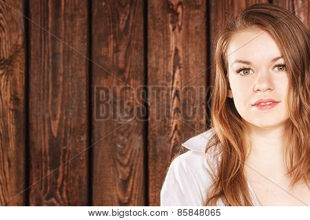 Portrait of  girl on background wooden wall