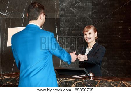 Receptionist at work behind the counter