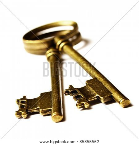 Old keys laying on top of white background isolated