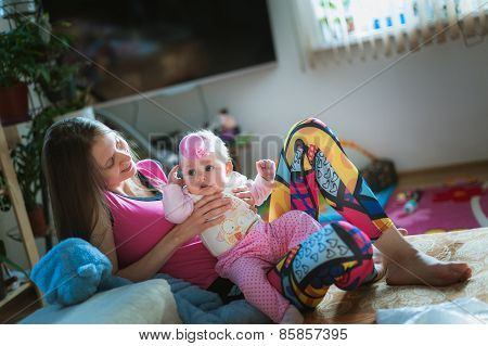 Image of young mam with cute little daughter in his arms