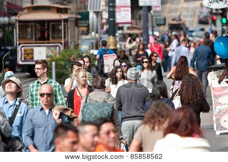 Crowd Of People Walk Among Trolley Cars In San Francisco