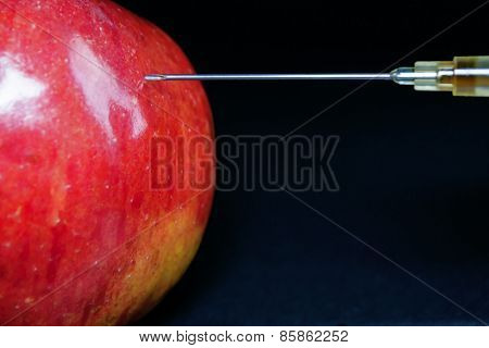 Hypodermic Needle Injecting A Red Apple
