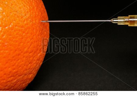 Hypodermic Needle Injecting An Orange