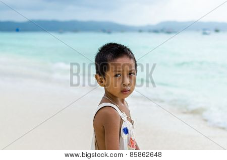 Young Impoverished Asian Boy At Exotic White Beach On Boracay, Philippines