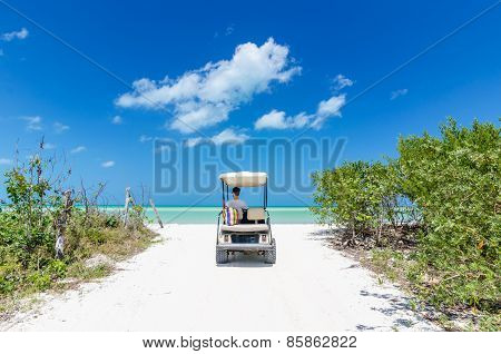 Young Man Driving On A Golf Cart At Tropical White Sandy Beach