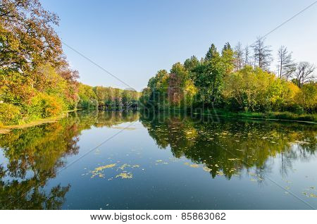 Attractive Autumn Landscape With Beautiful Reflection Of Woods Foliage Over Lake