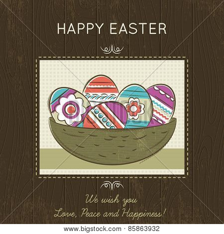 Easter Card With Nest Full Of Colored Eggs On Wooden Background.