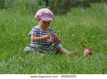 Young Beautiful Baby Girl Sitting On A Grass