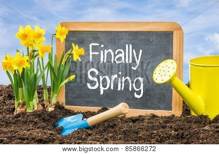 Sign In The Flower Bed With The Text Finally Spring