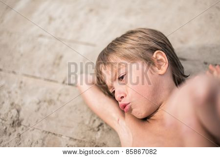Little boy tanning on wooden deck at the lake on hot summer day