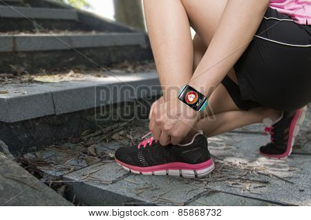 Sport Woman Tying Shoelaces Wearing Health Sensor Smartwatch With Trail