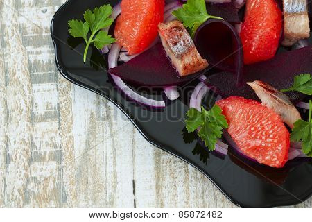 Dish With A Salad Of Herring, Beetroot And Grapefruit On A Wooden Background