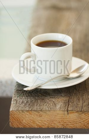 Cup Of  Coffee On The Edge Of A Wooden Table