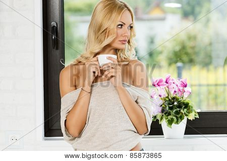 Woman Looking Out Window With Hot Coffee