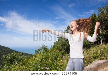 Young woman stands on a hilltop points into the distance