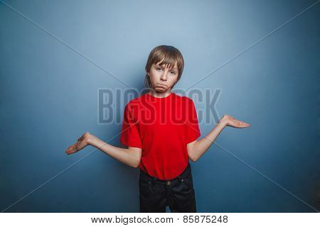 boy, teenager, twelve years in the red shirt spread his hands, t