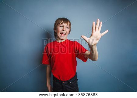 Boy, teenager, twelve years old, in a red shirt, showing hand