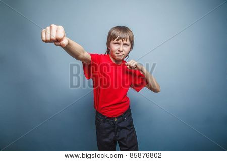 Boy, teenager, twelve years  red  in shirt, showing  fists