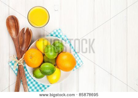 Citrus fruits. Oranges, limes and lemons and orange juice. Over wooden table background with copy space