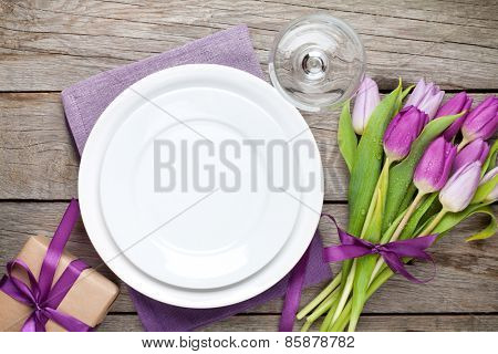 Purple tulip bouquet and plate on wooden table. Top view with copy space
