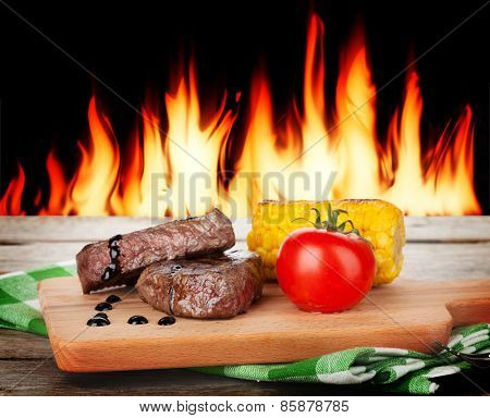 Steak with grilled vegetables on wooden table and fireplace