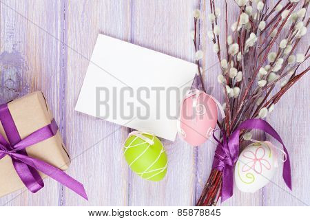 Greeting card, pussy willow and easter eggs over wooden table background with copy space
