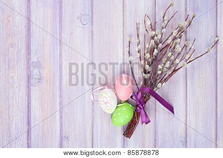Pussy willow and easter eggs over wooden table background with copy space