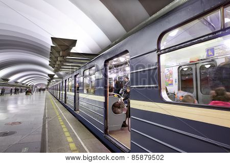 Blue Train With Passengers Standing Near Platform To Subway Station.