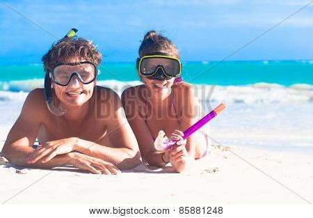 Beach travel couple having fun snorkeling, lying on summer beach sand with snorkel equipment