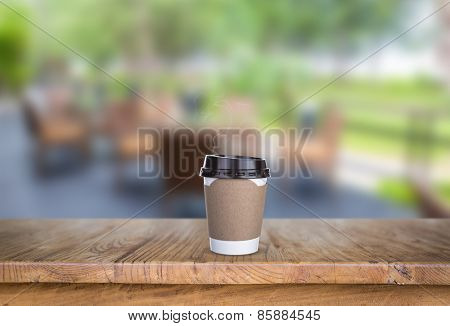 Paper cup of coffee on Wood table at restaurant