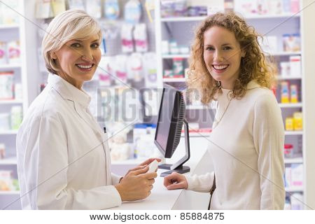 Pharmacist and costumer smiling at camera at pharmacy