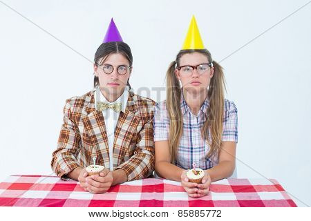 Unsmiling geeky hipsters celebrating birthday on white background