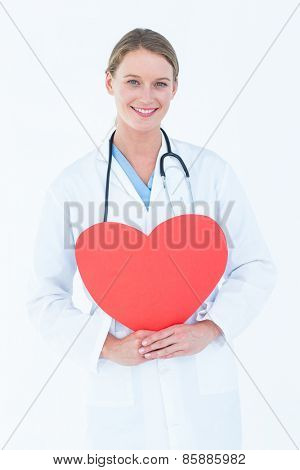 Doctor holding red heart card on white background