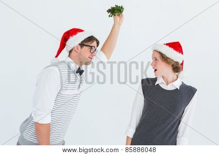 Geeky hipster holding mistletoe on white background