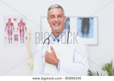Happy doctor holding clipboard and smiling at camera in medical office