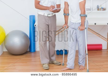 Doctor showing clipboard to his patient with crutch in medical office