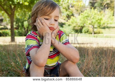 Sad little boy in the park on a sunny day