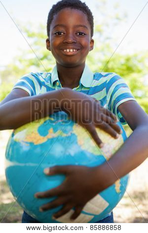 Cute little boy with globe on a sunny day