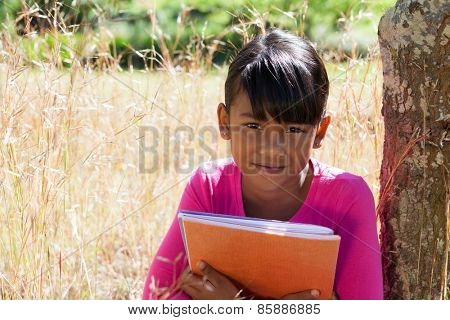 Cute little girl reading in park on a sunny day