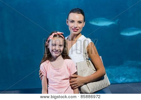 Happy mother and daughter by tank at the aquarium