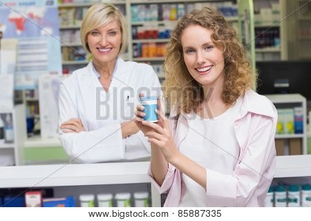 Costumer showing medicine jar at pharmacy